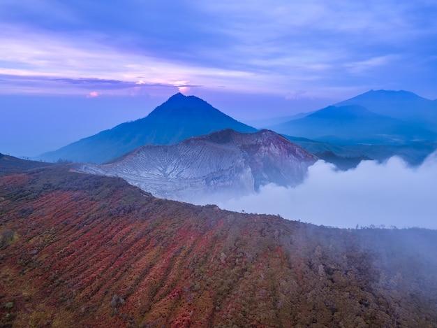 인도네시아. 발리 섬. 활화산 ijen에서 이른 아침. 열대 식물과 산 너머로 새벽에 경사. 조감도