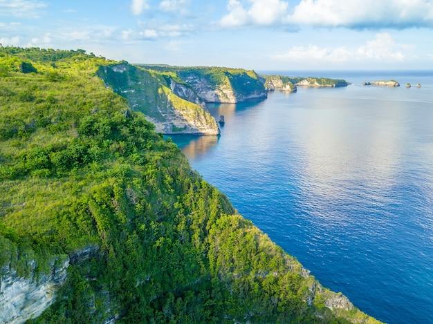 인도네시아. penida 섬의 해안. 바위에 정글. 푸른 하늘에 구름. 조감도