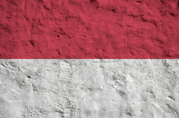 Флаг индонезии изображен яркими красками на старой рельефной штукатурке стены.