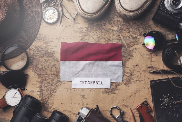 Indonesia flag between traveler's accessories on old vintage map. overhead shot