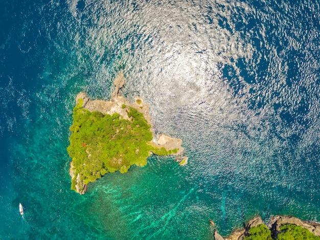 インドネシア。ジャングルが生い茂った小さな岩の無人島。近くのモーターボート。航空写真