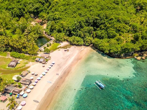 인도네시아. 페니 다 섬. 열대 우림으로 둘러싸인 푸른 물이있는 작은 해변. 보트와 사람. 조감도