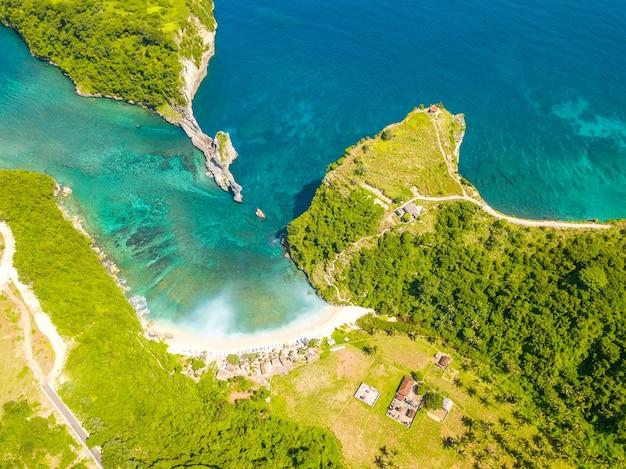 인도네시아. 페니 다 섬. 나무가 우거진 산으로 둘러싸인 빈 해변. 조감도