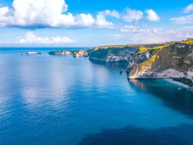 インドネシア。ペニダ島。海岸の崖の上の晴れた天気。雲と青い空。航空写真