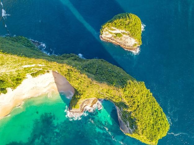 インドネシア。熱帯の島と野生のビーチの岩の多い海岸。垂直下向きの空中写真