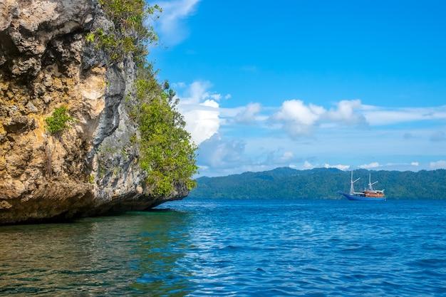 Индонезия. скалистый берег тропического острова в солнечную погоду. тропический лес на склоне. яхта на расстоянии