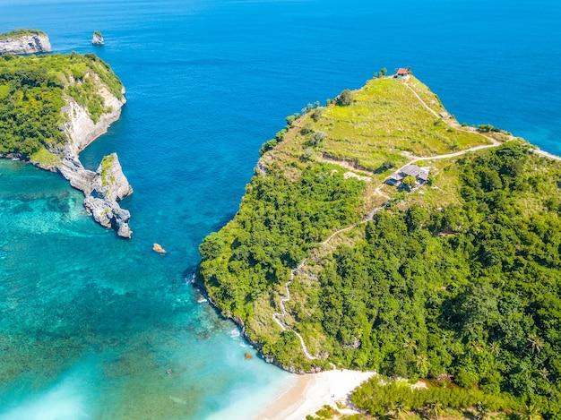 インドネシア。熱帯の島の岩の多い海岸。ターコイズブルーの水と小さなビーチ。崖の上にあるいくつかの小屋と斜面に沿った階段。航空写真