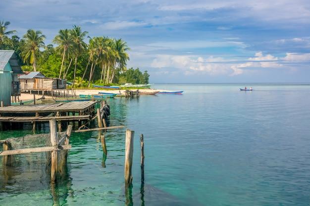 인도네시아. 열대 섬의 해안에 여러 건물과 보트. 수평선까지 광대 한 바다
