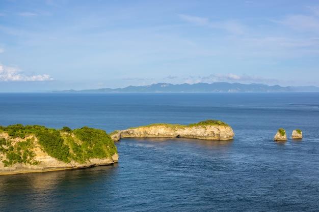 Индонезия. пролив между островами. день. скалистый берег с джунглями и двумя небольшими островками.