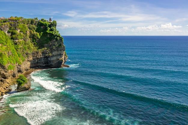 인도네시아. 맑은 날씨와 바다 위에 구름. 바다에 높은 절벽. 상단에 사원 단지