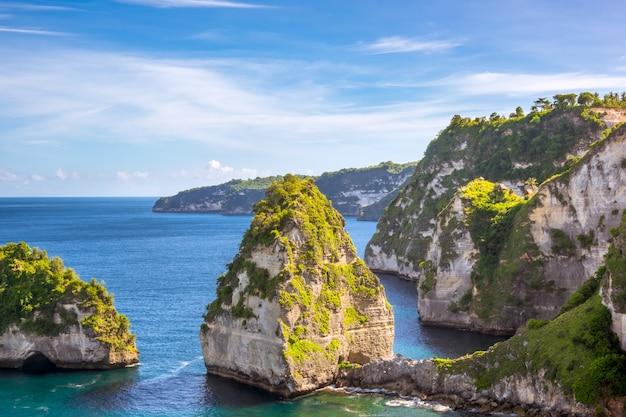 インドネシア。岩だらけの島の海岸。熱帯雨林の間の崖の上にあるいくつかの小屋