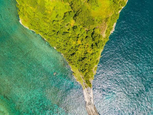 インドネシア。ジャングルに覆われた小さな島の先端。垂直下向きの空中写真