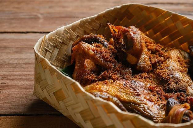 インドネシアの伝統料理。木製のテーブルの上に竹の箱を編んだアヤムゴレンカラサン