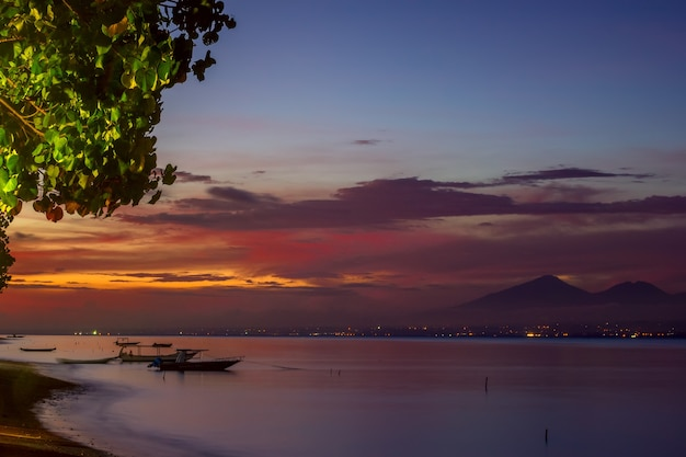 インドネシア。穏やかな水の上にボートがある熱帯の湾。日没後の色付きの空