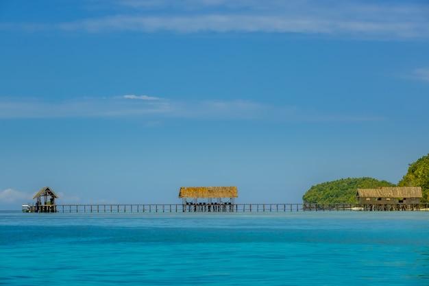 인도네시아. 열대 섬. 이른 저녁. 긴 목조 부두와 여러 창고
