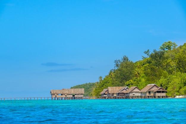 Индонезия. тропический остров ранним вечером. длинный деревянный причал и несколько хижин на сваях в воде