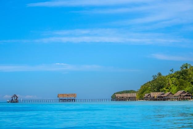 Индонезия. тропический остров ранним вечером. несколько хижин на сваях в воде и длинная деревянная пристань.