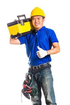 Индонезийский азиатский строитель или строитель со шлемом и поясом для инструментов, сидя на ящике для инструментов