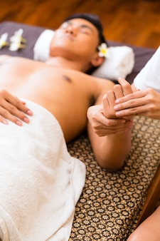 Indonesian asian man in wellness beauty spa having aroma therapy hand massage with essential oil, looking relaxed
