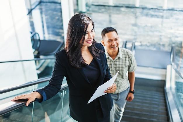 ジャカルタのオフィスビルのエスカレーターを上るインドネシアのビジネスマン