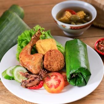 インドネシア料理:nasi timbel komplit、バナナの葉で包んだ伝統的なスンダ料理、フライドチキン、テンペ、豆腐、サユールアッサム、チリソースを添えて