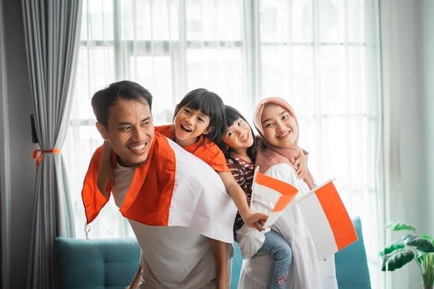 子供と一緒に家で独立記念日を祝うインドネシアの家族のイスラム教徒