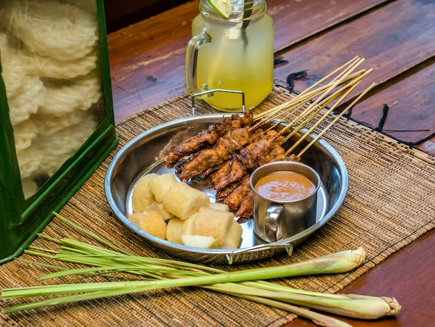 Indonesian food satay served with peanut sauce and rice cake roll
