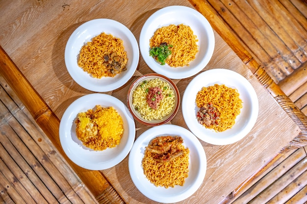 Indonesian instant noodles are served in white plates and arranged in such a way on the table.