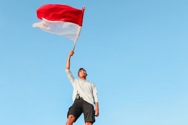 Indonesian male standing and waving indonesian flag with sky background