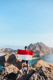 Indonesian man holding indonesia flag at labuan bajo