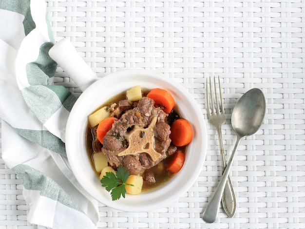 Индонезийский суп из бычьих хвостов или бунтут из супа на белой миске, изолированные