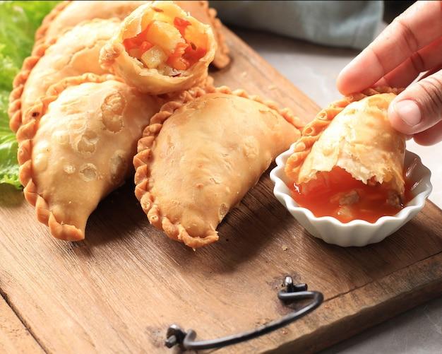 차와 함께 하얀 접시에 제공되는 인도네시아 파스텔 케이크. 카레 퍼프(카리팝)나 잘랑코트 마카사르로 인기.. 매운 소스 삼발과 함께 먹음