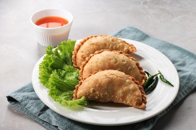 차와 함께 하얀 접시에 제공되는 인도네시아 파스텔 케이크. 카레 퍼프(karipap) 또는 jalangkote makasar로 인기가 있습니다.