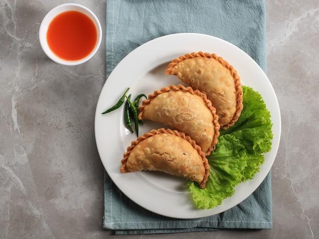 お茶と一緒に白いプレートで提供されるインドネシアのパステルケーキ。カレーパフ(カリパップ)やジャランコートマカッサルとして人気。