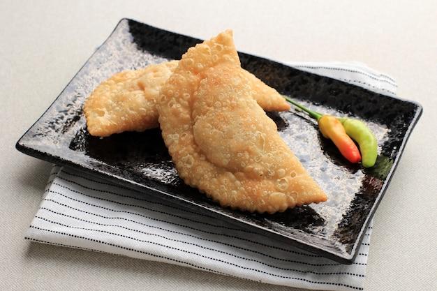 차와 함께 하얀 접시에 제공되는 인도네시아 파스텔 케이크. 카레 퍼프(karipap) 또는 jalangkote makasar로 인기