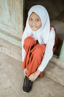 Indonesian primary school student getting ready to school in the morning tying shoes in front of the house