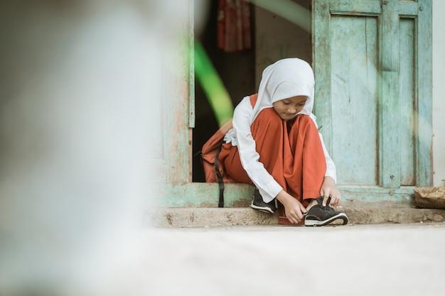 Индонезийская ученица начальной школы утром собирается в школу и завязывает обувь перед домом