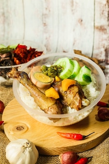 Indonesian rice bowl with egg and topping and fresh vegetables