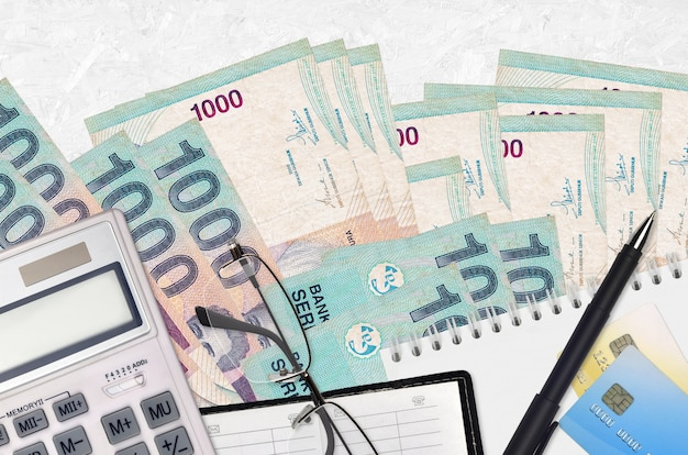 Indonesian rupiah bills and calculator with glasses and pen