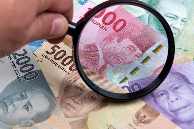 Индонезийская рупия в увеличительном стекле на фоне бизнеса