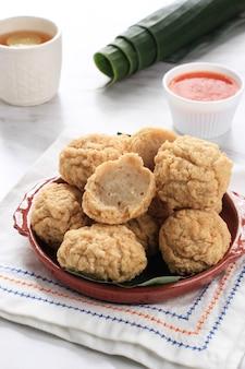 Индонезийская закуска: баксо горенг или фрикадельки во фритюре. сделано из курицы, мяса или креветок с мукой. подается с острым соусом