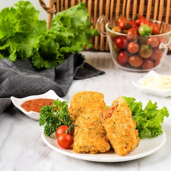 Indonesian snacks: fried risoles or risol vegetable with minced meat. served with chili sauce and mayonaise, garnish with fresh parsley.