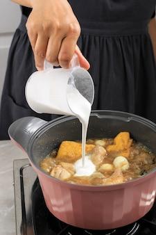 インドネシア/タイの家庭料理プロセス、女性の手でココナッツミルクを鍋に注ぎ、インドネシア/タイスタイルのカレーを作る、オポールアヤム、グライ、カリ、またはカレと呼ばれる伝統的なアジアのグルメ