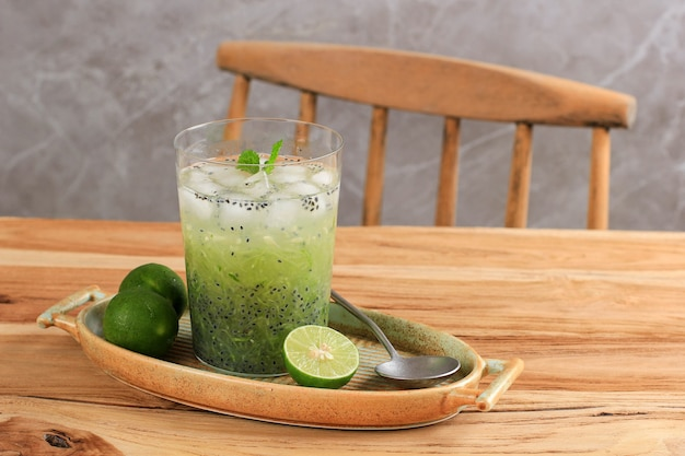 細かく刻んだキュウリ、ライムジュース、バジルの種から作られたインドネシアのベジタリアンドリンクes timun serutは、木製のテーブルの透明なガラスの上で提供されます