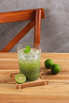 Indonesian vegetarian drink es timun serut made from shredded cucumber, lime juice, and basil seeds, served on clear glass on wooden table