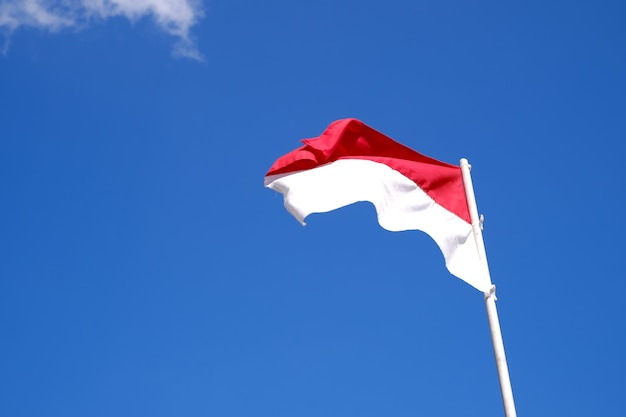 Indonesias red and white flag flying against blue sky