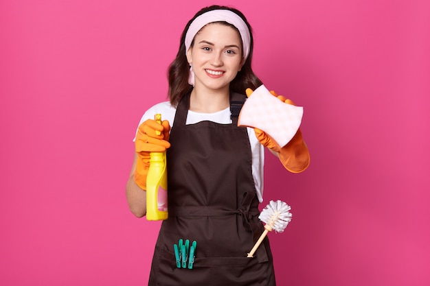 Indooe shot of woman holding yellow mop and detergent spray
