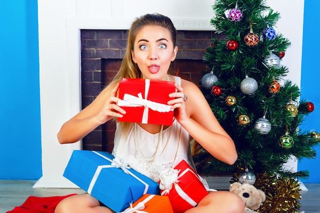 Крытый яркий портрет забавной молодой блондинки, сидящей дома возле новогодней елки