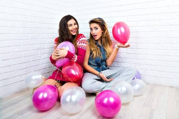 Indoor bright portrait of two funny bet friends sister hipster womans, going crazy, party time, pink balloon, showing v science, hugs and kisses, make up, sweaters, amazing smile.