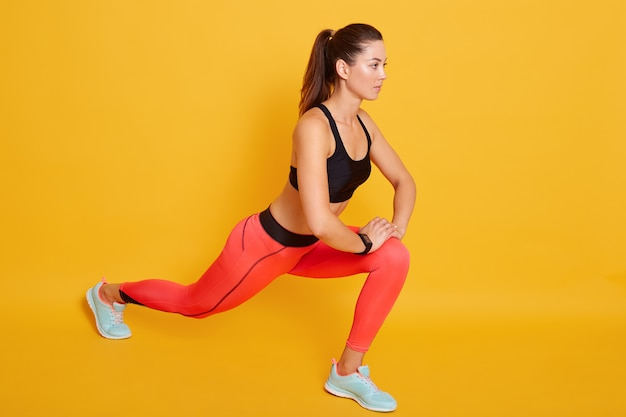 Indoor brunette young slim woman wearing stylish sports clothing stretching in gym, young female doing warmup stretching workout, isolatedon yellow. fitness concept.